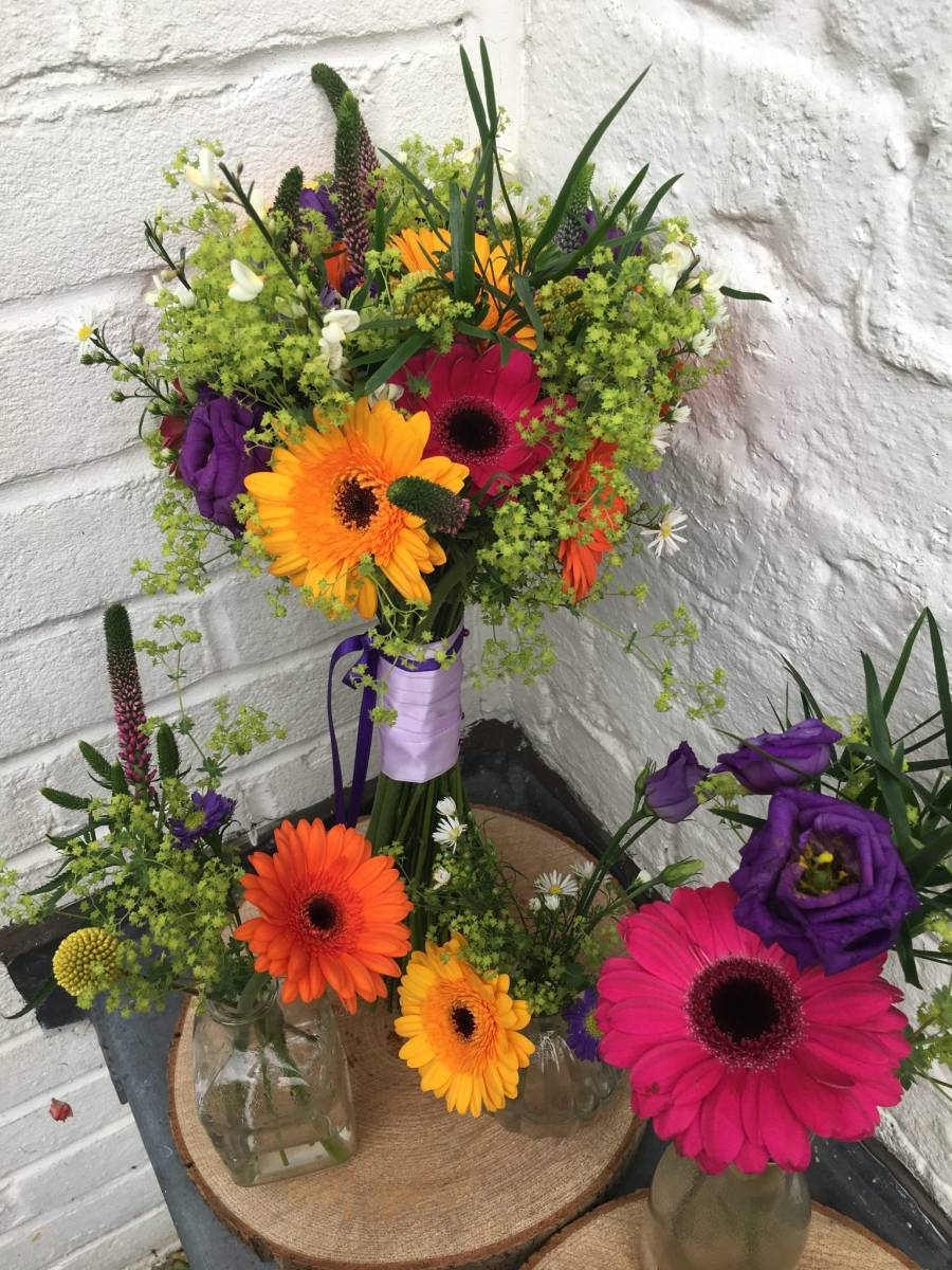 Bold & bright bouquet of germini & alchemila with table posies